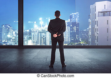 Back view of asian businessman looking the city