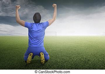 Back view of asian footballer man celebrate his goal