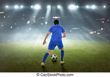 Back view of asian footballer with the ball
