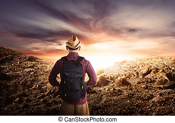 Back view of asian hikers man with hat standing on rocky mountains