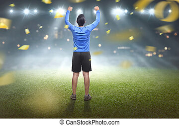Back view of asian man celebrating his victory