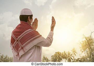 Back view of asian muslim man in white cap praying