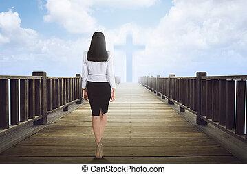 Back view of asian woman walking to cross shape