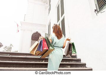 Back view of asian woman with shopping bags walking