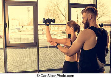 Back view of athletic man training young sporty woman with dumbbells in gym
