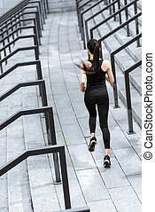 Back view of athletic young woman in sportswear running on stadium stairs