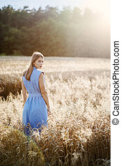 Back view of attractive blonde woman in blue dress in wheat field.