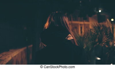 Back view of attractive brunette woman walking late at night. Attractive girl goes through the city centre alone.
