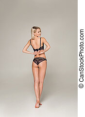 back view of attractive sexy girl taking off black lingerie, isolated on grey