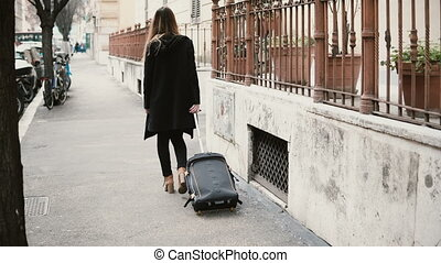 Back view of attractive woman with suitcase walking on the street. Businesswoman are going through the arch.