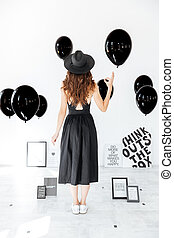 Back view of attractive young woman standing and holding balloon