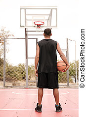 Back view of basketball player standing and holding ball