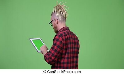 Back view of bearded hipster man with dreadlocks using...