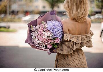 Back view of beautiful blonde woman in beige dress holding a romantic bouquet of flowers in purple tones