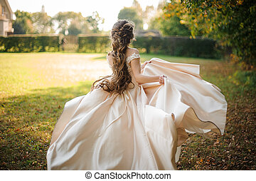 Back view of beautiful bride spinning in a wedding dress dancing on the green field