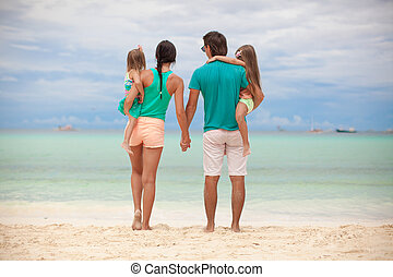 Back view of beautiful family with two daughters at exotic...