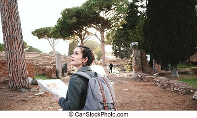 Back view of beautiful tourist girl with backpack and map exploring ancient sunny amphitheater ruins in Ostia, Italy.