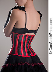 Back view of beautiful woman in corset and bra embracing herself