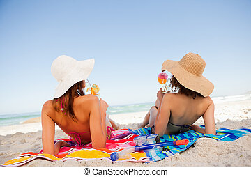 Back view of beautiful women sunbathing on beach towels ...