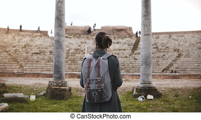 Back view of beautiful young female tourist with backpack and map exploring ancient amphitheater ruins in Ostia, Italy.