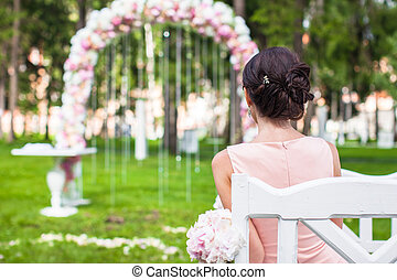 Back view of beautiful young woman in a long dress at the ceremony outdoors