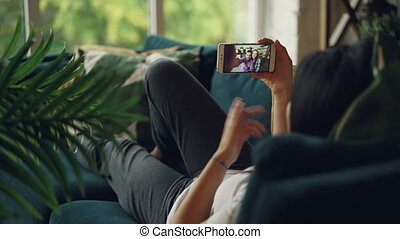 Back view of black-haired lady lying on sofa at home and making video call online communicating with friends cute couple. People are talking and gesturing sharing news.
