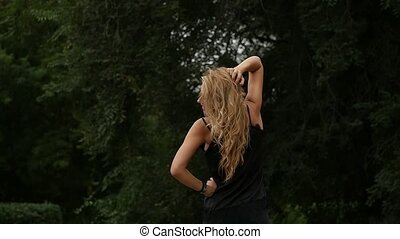back view of blonde woman on nature background. Beautiful girl poses with flying hair. slow motion
