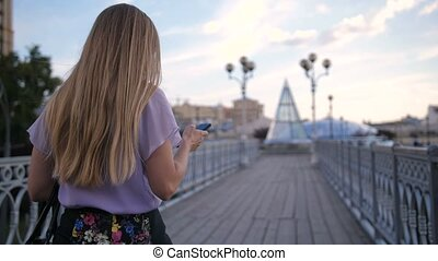Back view of blonde woman walking with cellphone