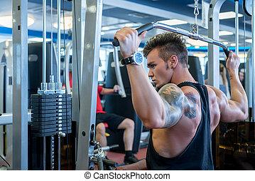Back view of bodybuilder exercising on simulator