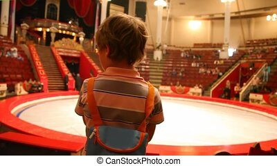 back view of boy stands against arena in circus after performance
