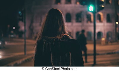 Back view of brunette woman walking late at night in Rome, Italy. Girl cross the road at crosswalk near the Colosseum.