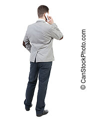 back view of business man in suit  talking on mobile phone.