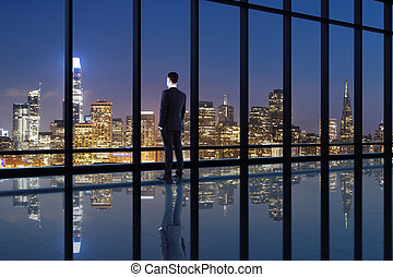 Back view of businessman looking into distance of window