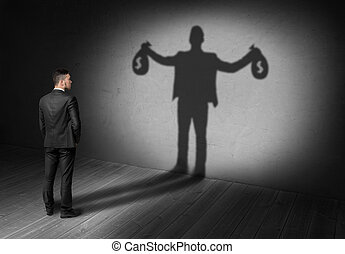 Back view of businessman looks to his shadow and sees rich future