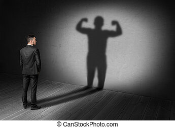 Back view of businessman looks to shadow with strong his display in future