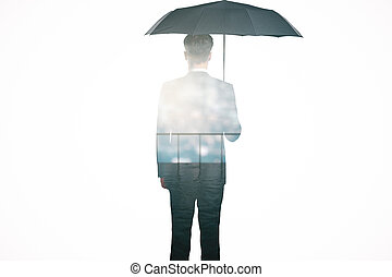 Protection concept - Back view of businessman with umbrella...