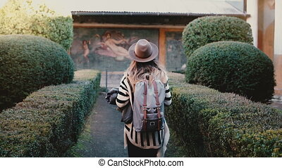 Back view of Caucasian tourist girl with backpack exploring...