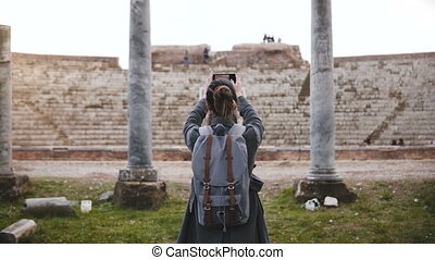 Back view of Caucasian tourist girl with backpack taking...