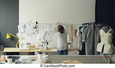 Back view of creative female tailor taking sketches from...