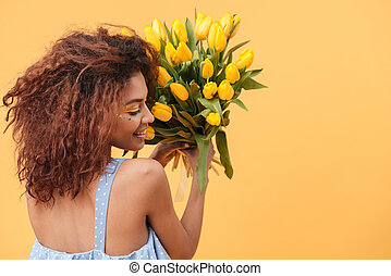 Back view of Cute African woman holding bouquet  flowers