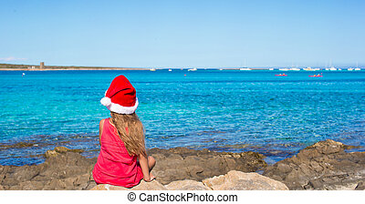 Back view of cute little girl in Santa hat on the beach -...