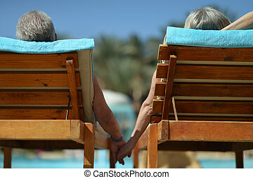 Back view of Elderly couple lying by pool at hotel resort