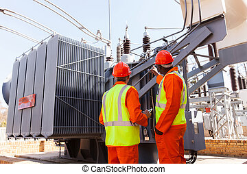 electricians standing next to a transformer - back view of...