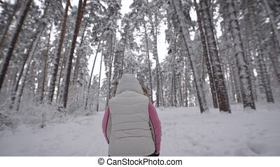 Back view of energetic woman in white waistcoat and black trousers doing active nordic in the forest. Female athlete stepping quickly with ski poles in winter outdoors demonstrating healthy lifestyle.