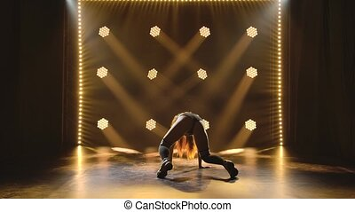 Back view of erotically dancing young woman twerking and bending her body. Shot in a dark studio with neon lights in the background. Slow motion