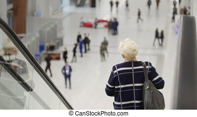 back view of escalator. Aged woman goes down.