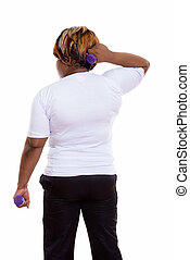 Back view of fat black African woman exercising with dumbbells r