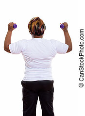 Back view of fat black African woman with both dumbbells raised