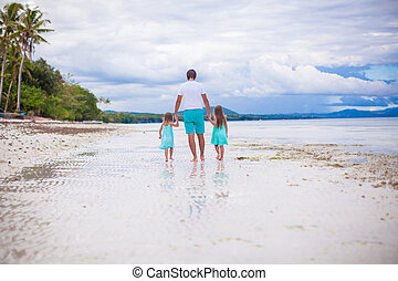 Back view of father and his two little daughters walking by the sea