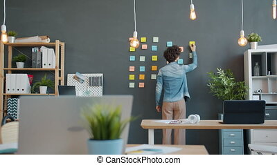 Back view of female office worker writing on colorful sticky...